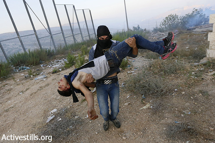 Palestnians carry Mohammad Qasem Hamamreh, after he was injured in the head with a tear gas canister at the early morning of July 23, during clashes with the Israeli army in the West Bank village of Husan, 2014. Mohammad, 19 years old, died in the hospital the day after (Mustafa Bader/Activestills.org)