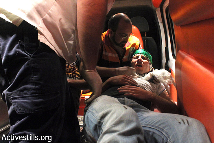 An injured Palestinian is being evacuated in an ambulance during clashes with the Israeli army following a demonstration against the attack on Gaza, Huwwara military checkpoint, Nablus, West Bank, the early morning of July 25, 2014. A 22 years old Palestinian was shot to death by the Israeli army with live ammunition and at least 3 were injured, the same day at Huwwara checkpoint. (Ahmad Al-Bazz/Activestills.org)