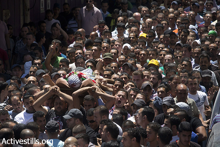 Mourners carry the body of killed Palestinian Mohammed al-Araj, 17, during his funeral at the Qalandiya refugee camp near the West Bank city of Ramallah, on July 25, 2014. Al-Araj was shot with live ammunition in the head the night before during clashes with Israeli army following a mass demonstration against the attack on Gaza. (Oren Ziv/Activestills.org)