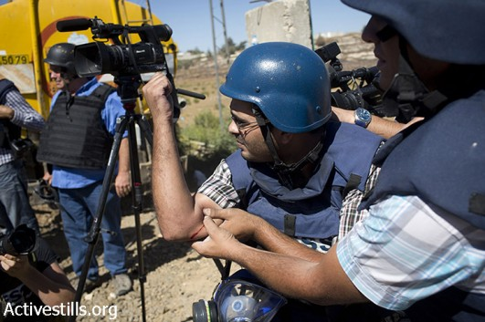 A member of the media holds his arm after being injured from a live bullet while covering Palestinian clashes with the Israeli army following a protest supporting Hamas against the Israeli attack on Gaza, on July 25, 2014, in the DCO checkpoint near Ramallah, West Bank.