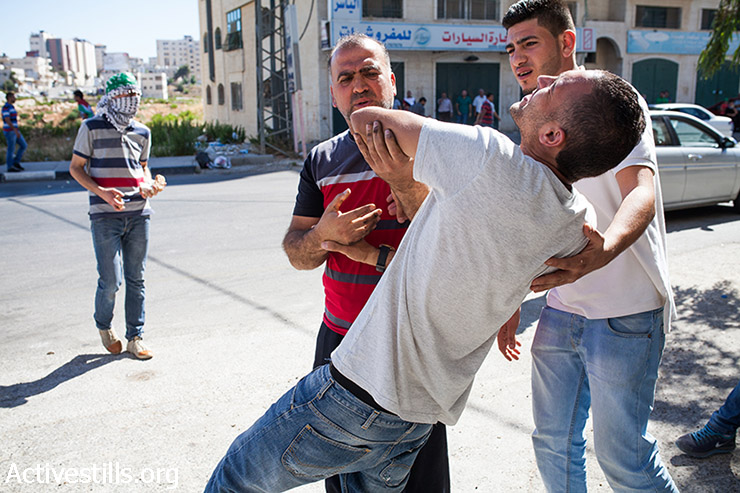 A protestor falls  after being injured from a live bullet while participating in a protest, supporters by Hamas, against the Israeli attack on Gaza, on July 25, 2014 in the DCO checkpoint near Ramallah, West Bank. (Yotam Ronen/Activestills.org)