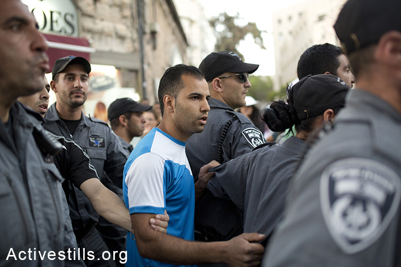 A Palestinian is escorted by Border Policemen after being attacked by a right-wing mob during riots that errupted following the finding of the bodies of three Israeli teenagers. (Tali Mayer/Activestills.org)