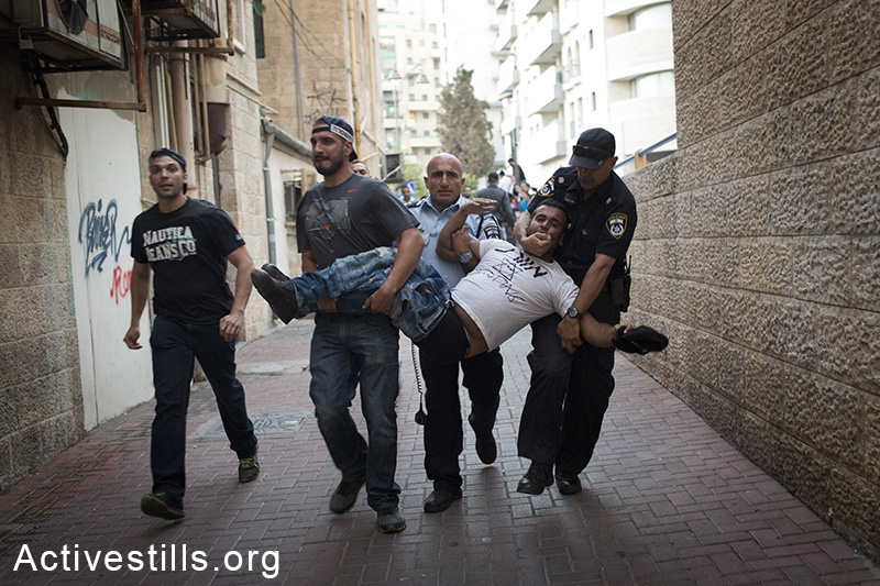 "Border Policemen arrest a right-wing protester wearing a T-shirt with the slogan ""death to terrorists,"" during riots that errupted following the finding of the bodies of three Israeli teenagers, West Jerusalem, July 1st, 2014. (Tali Mayer/Activestills.org)"
