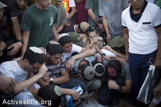 Family and friends of Eyal Yifrah, Gilad Shaar, and Naftali Fraenkel, three Israeli teenagers who were abducted over two weeks ago, take part in their funeral in the city of Modiin, Israel, Tuesday, July 1, 2014.  Tens of thousands of mourners arrived ro Modiin in central Israel for a funeral service for three teenagers found dead in the West Bank after a two week searches, raids and arrests in the West Bank, as Israel accused Hamas of abducting and killing the young men. (Oren Ziv/Activestills.org)
