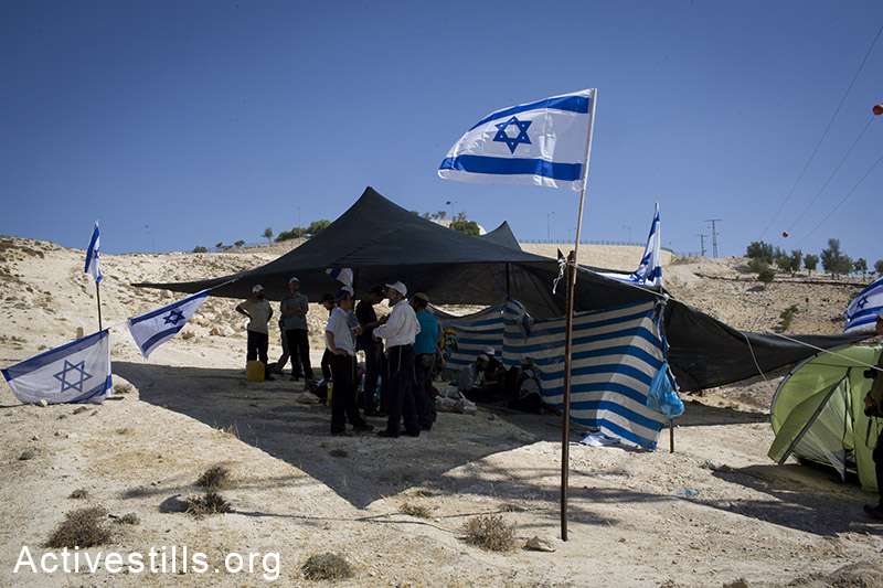 Israeli right-wing activists seen at the outpost they built in the E-1 area outside the settlement of Ma'ale Adumim in response to the murder of the three kidnapped Israeli teenagers on July 1, 2014. (Oren Ziv/Activestills.org)