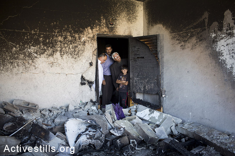 Palestinians inside the damaged family home of Amer Abu Aisheh, one of two Palestinians identified by Israel as suspected of the killing of three Israeli teenagers, after it was damaged by the Israeli army in the West Bank city of Hebron, Tuesday, July 1, 2014. (Oren Ziv/Activestills.org)