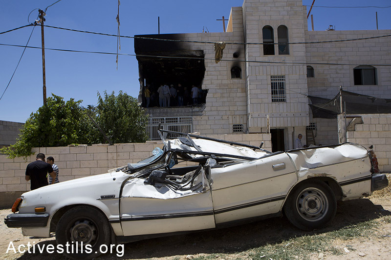 A damaged car is seen outside the family home of Amer Abu Aisheh, one of two Palestinians identified by Israel as suspects in the killing of three Israeli teenagers, Tuesday, July 1, 2014. (Oren Ziv/Activestills.org)
