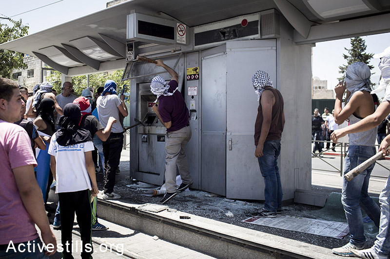 Palestinian youths brake the light-train station of Beit Hanina, during clashes that broke out in East Jerusalem following the suspected kidnapping and murder of a Palestinian teenager, East Jerusalem, July 2, 2014. Total of four journalists and a dozen protesters injured in the clashes. (Oren Ziv/Activestills.org)