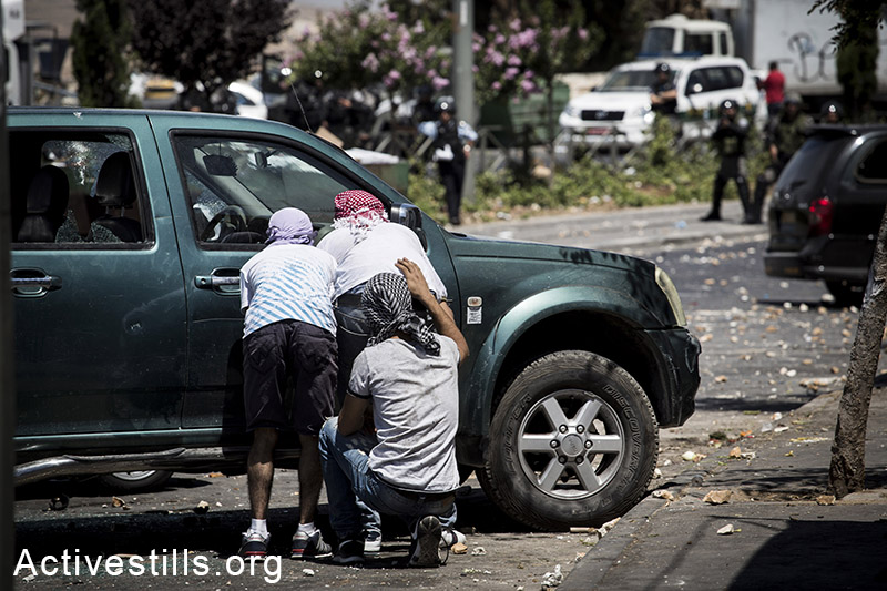 Palestinian youths take cover during clashes that broke out in East Jerusalem following the suspected kidnapping and murder of a Palestinian teenager, East Jerusalem, July 2, 2014. (Oren Ziv/Activestills.org)