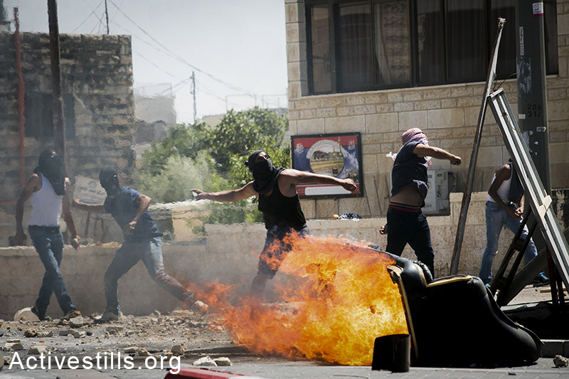 Palestinian youths clash with Israeli forces during a protest following the suspected kidnapping and murder of a Palestinian teenager, East Jerusalem, July 2, 2014. Total of four journalists and a dozen protesters injured in the clashes. (Oren Ziv/Activestills.org)