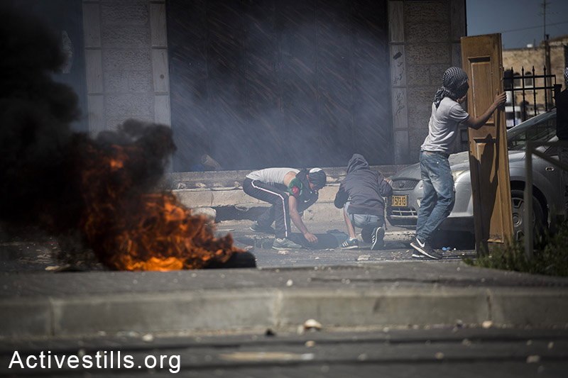Palestinian youths take cover during clashes following the suspected kidnapping and murder of Muhammad Hussein Abu Khdeir, East Jerusalem, July 2, 2014.  (Tali Mayer/Activestills.org)