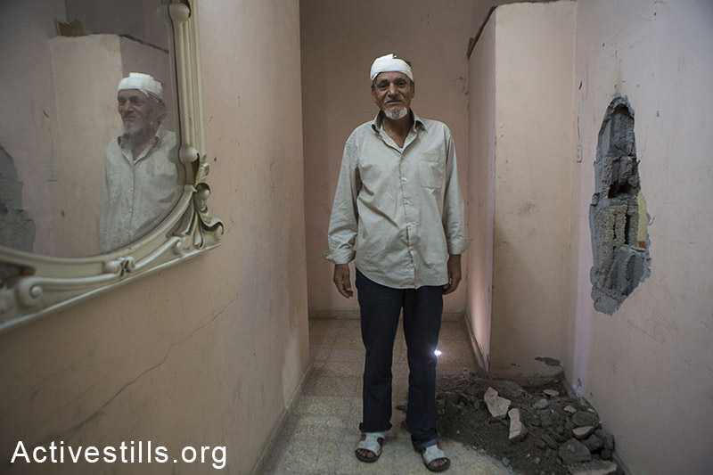 """Majeed Al-Zeem, 52 year old, stands next to an hole caused by a missile launched by a drone which caused his injury, Gaza city, July 14, 2014. The missile was launched by the Israeli army to warn the family that they are going to conduct an airstrike on the house next door, a policy known to be termed """"knock on the roof"""". Israeli attacks have so far killed more than 180 Palestinians."""