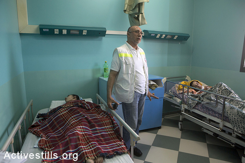 Doctor Basman Alashi, director of the el-Wafa hospital, is seen next to two paralized patients, in Al-shajaia'a area in the Eastern Part of Gaza city, July 15, 2014. One of the patients (left) 23 years old Yusra Abu Moussa has lived in the hosital since she was nine years old. The hospital was hit on Friday, July 11, 2014, by five missiles which caused considerable damage. The top floor was evacuated beforehand. fourteen patients who could not be evacuated remained at the hospital, and internationals stayed with them as human shields.As of July 15, 192 Palestinians have been killed and more than 1,400 have been injured. (Anne Paq/Activestills.org)