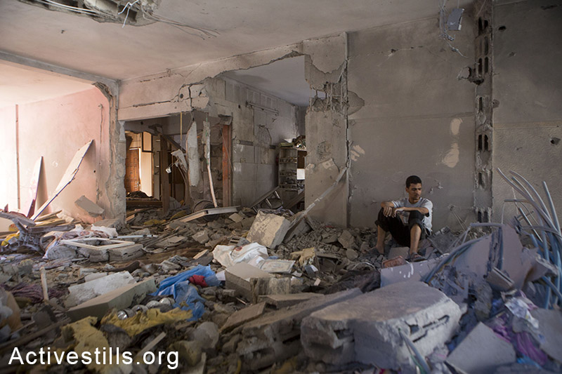 A man sits in a destroyed building which was attacked last night by Israeli airstrike, in Al Tuffah neighborhood, July 16, 2014. As of July 16th, 196 Palestinians have been killed in the Israeli attack on the Gaza Strip, and more than 1,400 have been injured. (Anne Paq/Activestills.org)