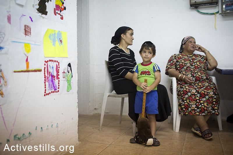 Woman and children sit inside a bomb shelter in the city of Ashklon, July 16, 2014. (Oren Ziv/Activestills.org)