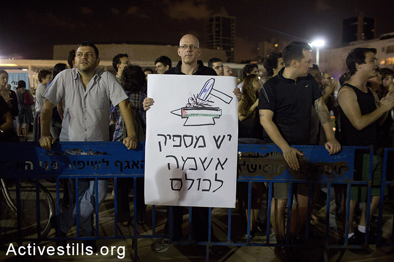 "Israeli left wing activists protest against the Israeli attack on Gaza, in central Tel Aviv, July 17, 2014. The sign reads: ""There is enough guilt for everyone"". Police arrested three right-wing protesters who tried to hurt left-wing activists, as hundreds were protesting against the attack. Right-wing activists held a counter demo, calling for the killing of Arabs and for more use of force in Gaza. (Oren Ziv/Activestills.org)"