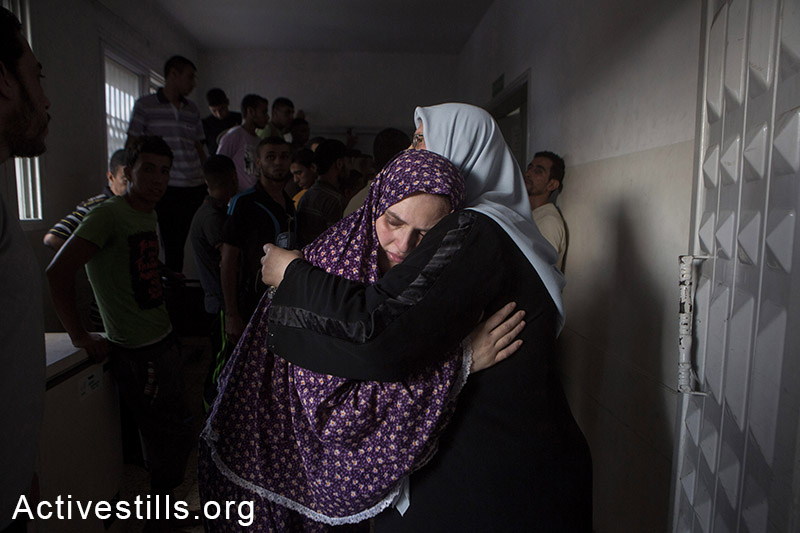 Mother (left) of Jihad Issam Shuhaibar (8), and Wasim Issam Shuhaibar (7), two of the children killed in an Israeli airstrike on the Sabra neighborhood of Gaza City, is comforted by a relative at al-Shifa hospital, July 17, 2014. The third victim of the airstrike that hit the children while they were playing on the roof of their house, was their cousin, 10-year-old Afnan Tariq Shuhaibar. (Anne Paq/Activestills.org)