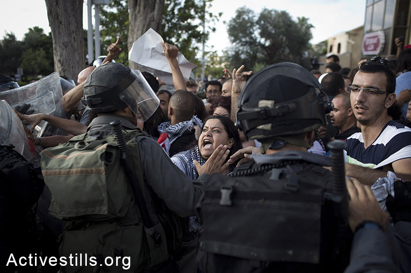 Israeli policemen push back protesters, as Palestinians living in Israel and left wing activists protest against the Israeli attack on Gaza in downtown Haifa, July 18, 2014. Israeli police arrested 28 activists, as protesters took to the streets and blocked roads, calling for an end to the attack. (Oren Ziv/Activestills.org)
