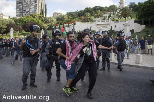 Israeli policemen arrest protesters as Palestinians living in Israel and left-wing activists protest against the Israeli attack on Gaza in downtown Haifa, July 18, 2014. Israeli police arrested 28 activists, as protesters took to the streets and blocked roads calling for an end to the attack. (Fiaz abu-Ramele/Activestills.org)