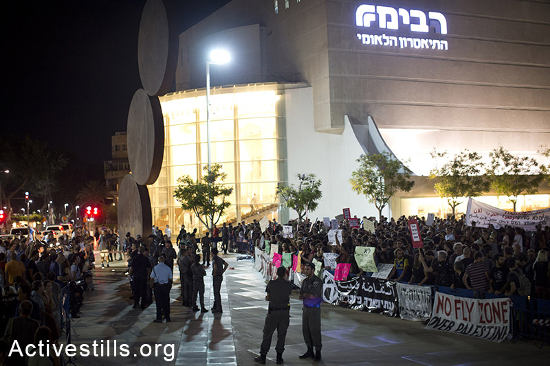 Israeli right-wing demonstrators (left) protest in front of left-wing activists, as they take part in a protest against Israel's attack on Gaza, in central Tel Aviv, July 19, 2014. Right-wing activists tried to attack left wing activists during the protest, police arrested at least five right-wing protesters. (Oren Ziv/Activestills.org)