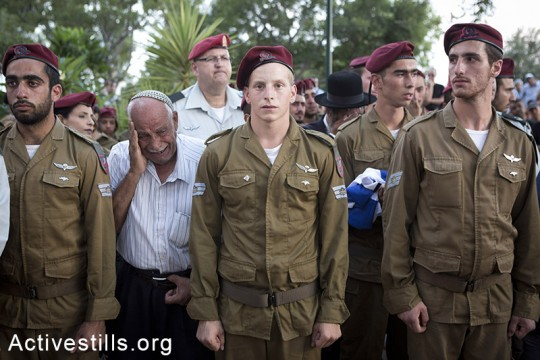 Soldiers and relatives mourn at the grave of Israeli Sergeant Banaya Rubel during his funeral on July 20, 2014 in Holon, Israel. Sergeant Rubel was killed along with another Israeli army soldier on the 12th day of operation 'Protective Edge,' when Hamas militants infiltrated Israel from a tunnel dug from Gaza and engaged Israeli soldiers. (Oren Ziv/Activestills.org)