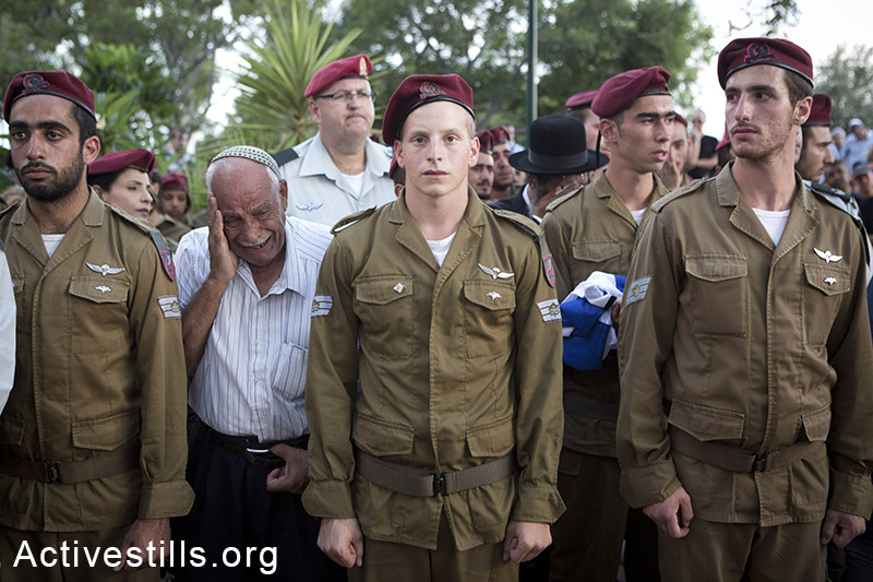 Soldiers and relatives mourn at the grave of Israeli Sergeant Banaya Rubel during his funeral on July 20, 2014 in Holon, Israel. Sergeant Rubel was killed along with another Israeli army soldier on the 12th day of the attack. (Oren Ziv/Activestills.org)