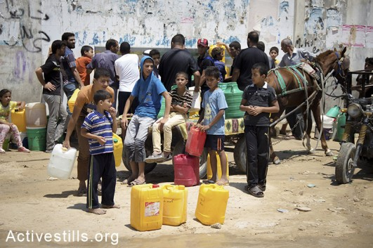People of Khan Younis gather at a water well to fill some plastic jugs of safe drinking water, Gaza Strip, July 21, 2014. Israeli attacks have killed 566 Palestinians in the current offensive, most of them civilians. (Basel Yazouri/Activestills.org)