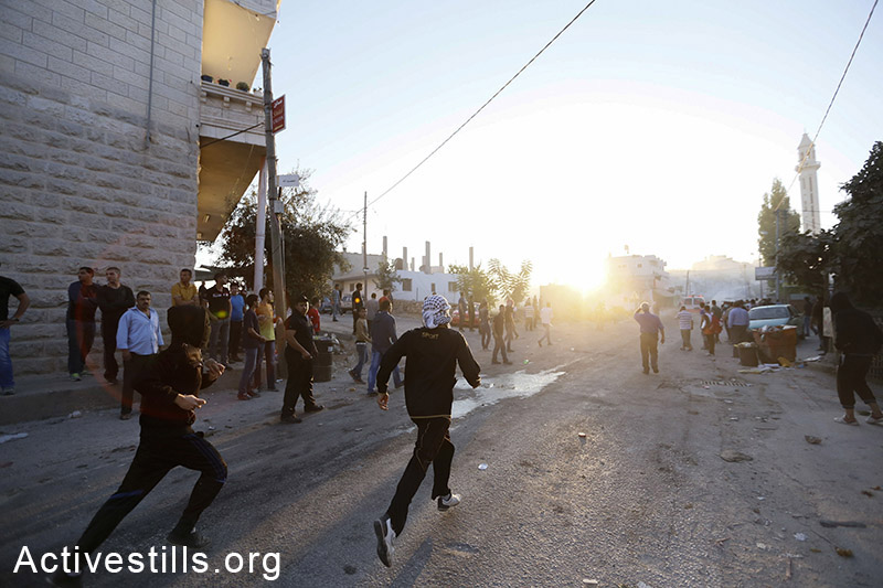 Clashes between Palestinian youths and Israeli soldiers following the killing of Mahmud al-Hamamra, 33, shot to death by Israeli soldiers, July 22, 2014. Mahmud was shot during a protest against the Israeli attack on the Gaza strip in the West Bank village of Husan, near Bethlehem. (Mustafa Bader/Activestills.org)