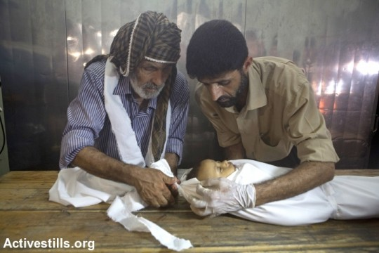 Palestinians prepare the body of a baby in Kamal Edwan Hospital's morgue after an attack on Beit Hanoun elementary school killed at least 17 people, Jabalyia, Gaza Strip, July 24. The school was being used as a shelter by 800 people at the time (photo: Anne Paq/Activestills)