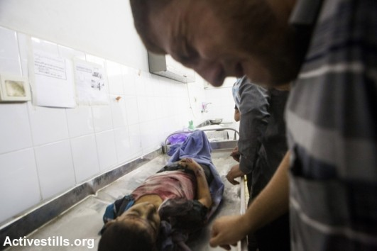 A relative cries over the body of one of the children killed by an Israeli attack on a playground in al-Shati refugee camp, Gaza city, July 28, 2014. Reports indicate that 10 people, mostly children, were killed and 40 injured during the attack which took place on the first day Eid. (photo: Activestills)
