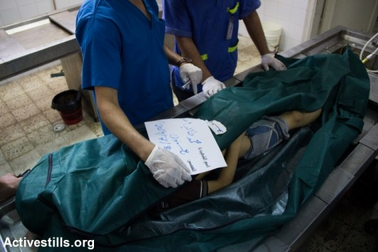The bodies of Palestinians lie in the Al Shifa Hospital morgue in Gaza City following an attack on an UNRWA school in Jabaliya, July 30, 2014 (photo: Activestills)