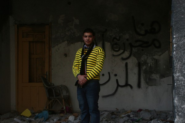 """Amjad Muzannar stands in the room where his brother and grandmother were killed by an Israeli airstrike on November 18, 2012. The """"target"""" of the airstrike was the adjacent Al-Dalu family home, in which 10 people were killed, including five women and four children.  (Photo by Lara Aburamadan)"""