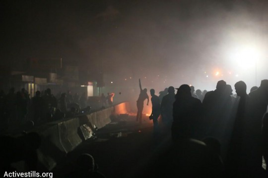 Thousands of Palestinians marches from Ramallah to Qalandiya Checkpoint and in East Jerusalem where they clashed with Israeli forces in protest of Israel's attacks on Gaza. (Oren Ziv/Activestills.org)