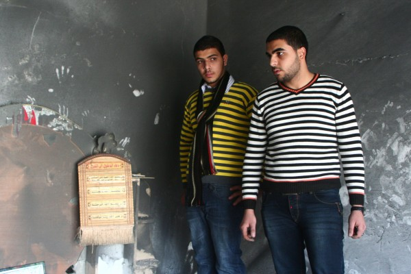 Abdullah's brothers, Haytham and Amjad, stand in the ashen shell of a bedroom in their family's destroyed home. (Photo by Lara Aburamadan)