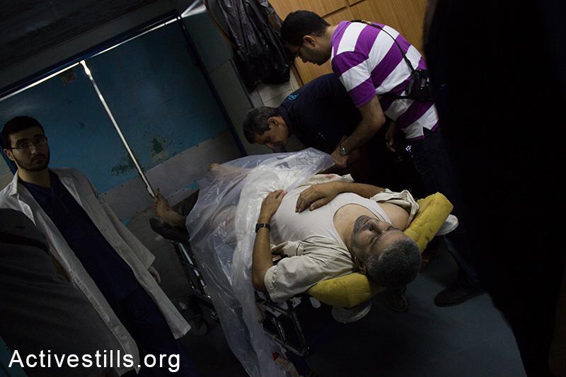 A body lays at the Al Shifa hospital as more bodies arrive from the Shejaiya area, July 20, 2014. (Basel Yazouri/Activestills.org)