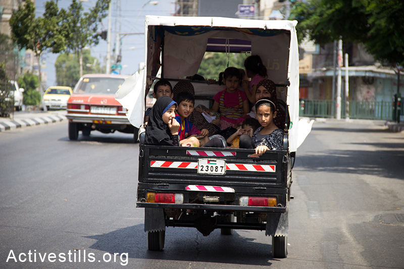 Gazans flee the Shejaiya area after Israeli tanks invaded the area, bombarding it heavly, causeing over 60 casulties and hundreds wounded, July 20, 2014.  (Basel Yazouri/Activestills.org)