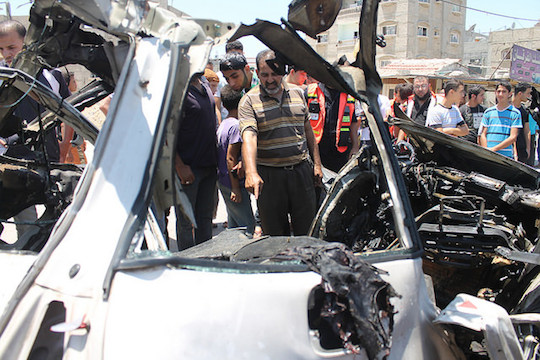 Gaza Civil Defense Directorate crews remove the wreckage of a car targeted by an Israeli airstrike in the northern Gaza Strip, July 10, 2014. The attack killed three men riding in the car who were taken to Kamal Udwan hospital. Two were identified as Mahmoud Waloud and Hazim Balousha. (Photo by Joe Catron)