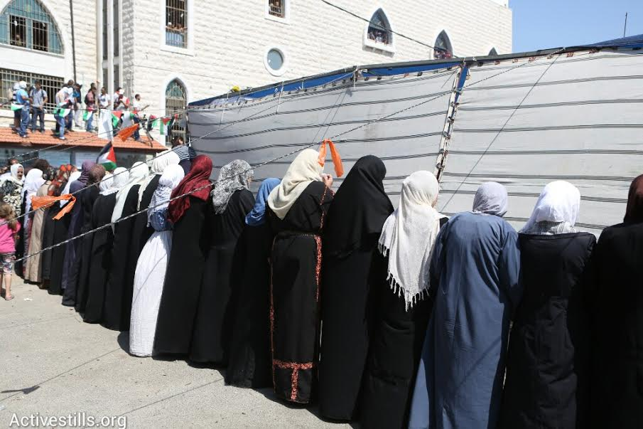 Palestinian women hide during clashes between youth and Israeli security forces in Shuafat. (photo: Oren Ziv/Activestills.org)