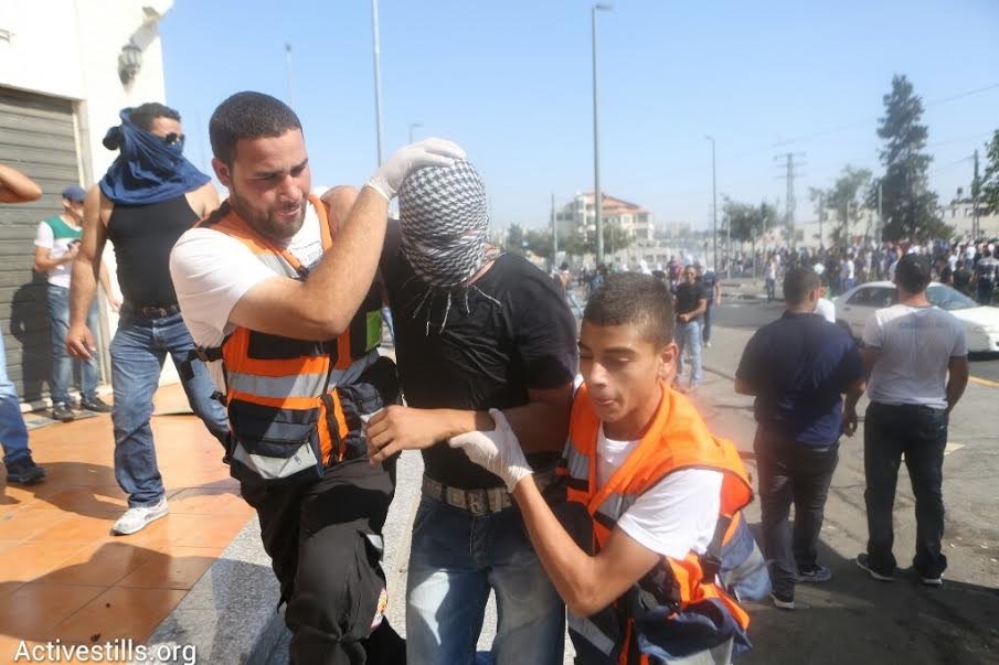 Palestinian paramedics help carry a protester across the street during clashes in Shuafat. (photo: Oren Ziv/Activestills.org)
