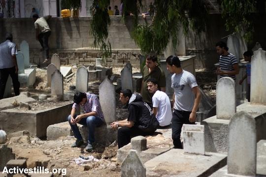 Palestinians mourn the death of Ibrahim Nabil Hamada, 23, who was killed during an Israeli attack, Al Shaja'ia cemetery, Gaza City, July 12, 2014. (Photo: Basel Yazouri/Activestills.org)