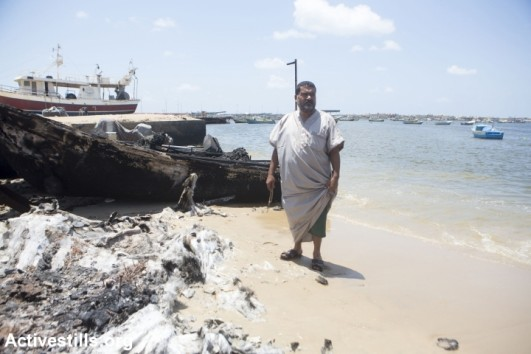 Sabri Baker, 53, a fisherman and father of 16 children, walks towards his destroyed boat in Gaza harbor, July 15, 2014. In 2012 his previous boat was confiscated by the Israeli army and was never returned. The boat was destroyed during an Israeli attack on July 11, 2014 (photo: Anne Paq/Activestills.org)