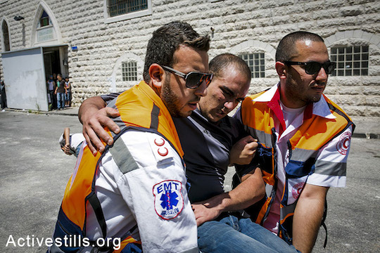 Palestinian medics evacuate a Palestinian protester during a protest following the suspected kidnapping and murder of a Palestinian teenager, East Jerusalem, July 2, 2014. (Yotam Ronen/Activestills.org)