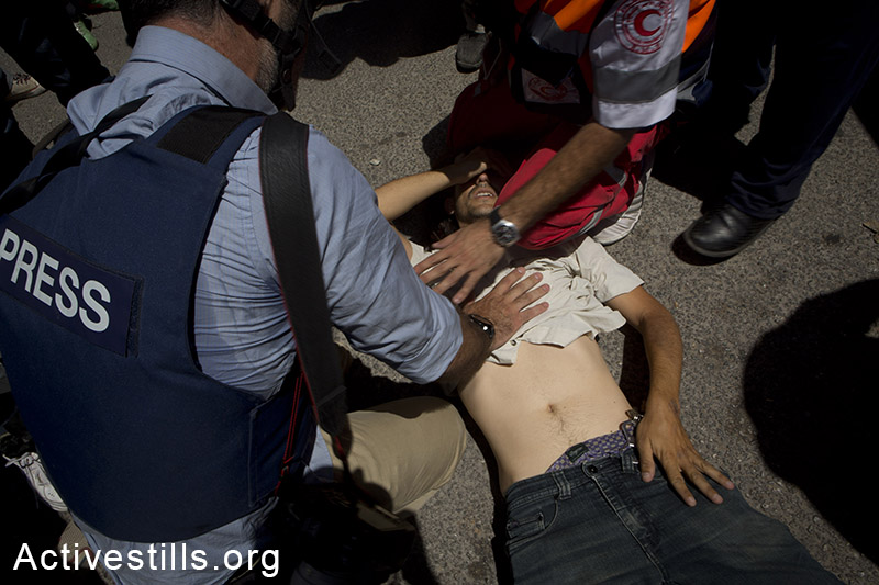 Activestills' Oren Ziv laying on the ground after getting shot in the neck with a black sponge bullet in the neck during clashes, following the suspected kidnapping and murder of a Palestinian teenager, East Jerusalem, July 2, 2014. (Activestills.org)