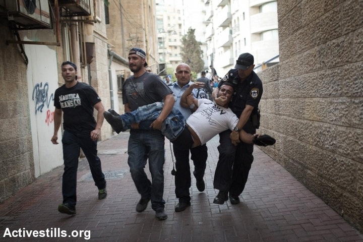 Policemen carry a right-wing protester during Tuesday night's clashes in Jerusalem. (photo: Activestills)