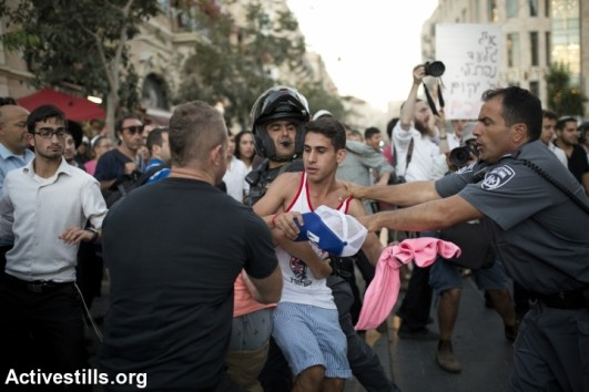 Policemen detain a young, right-wing protester during clashes in Jerusalem that erupted following the discovery of the bodies of three teenaged settlers near Halhul, West Jerusalem, July 1, 2014. The riots broke out during the funerals of Eyal Yifrah, 19, Gilad Shaar, 16, and Naftali Fraenkel, 16, who were kidnapped and killed in the West Bank. (photo: Activestills)