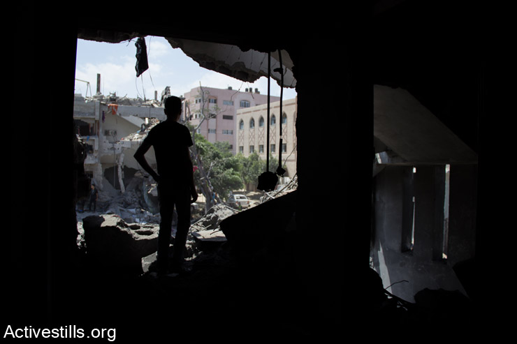 Palestinian man stands in his destroyed house overlooking the bombed  Shujaiyeh neigborhood, Gaza City, July 26, 2014. (Basel Yazouri/Activestills.org)