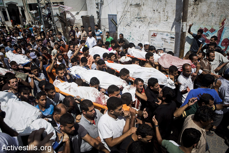 A funeral in Bani Suhaila for the 21 members of the Al-Najjar family, who were killed just before the ceasefire, east of Khan Younis, Gaza Strip, July 21, 2014. The Al-Najjar family fled their homes in Khuza'a to take refuge further west. Israeli attacks have killed more than 1,400 Palestinians in the current offensive, most of them civilians. Khuza'a has been under heavy attack and many people fled the village as the Israeli army physically occupied it. (Anne Paq/Activestills.org)