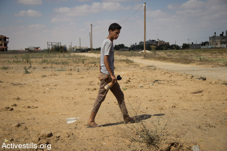 A Palestinian shows pieces of Israeli weaponry in Abasan al-Kabira village at the entrance to another village Khuza'a, East of Khan Yunis, July 26, 2014. During the ceasefire on 26 July, many Palestinians went back to Abasan al-Kabira to inspect the damage together with medics, who attempted to rescue the injured or collect bodies. Residents of adjacent Khuza'a could not enter, as Israeli soldiers fired warning shots. (Basel Yazouri/Activestills.org)