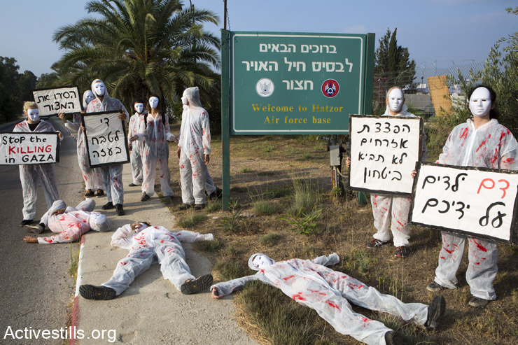 """Israeli women activists stage a protest against the attack on Gaza at Hatzor Air Force base, Israel, July 29, 2014. The activists wore white overalls stained with red paint and called on the Israeli government to stop the air strikes and bring an end to the siege on Gaza. They also expressed concern regarding the suffering of civilians in southern Israel. Signs in Hebrew read (from R to L): """"Blood of children on your hands,"""" """"Bombing civilians will not bring security,"""" """"Stop the massacre in Gaza"""" and """"Remove the siege."""" A few activists were detained by security forces. (Activestills.org)"""