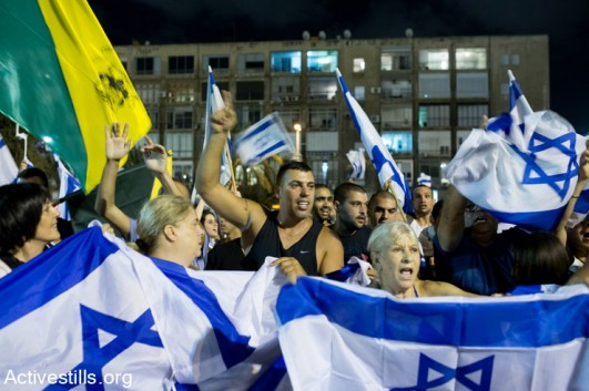 Right-wing demonstrators protest in front of a demonstration against the Israeli attack on Gaza, in Rabin Square, Tel Aviv, July 26, 2014. Right-wing activists protested nearby and attacked left-wing activists during and after the protest. One left-wing activists was hospitalized with a head injury. (Yotam Ronen/Activestills.org)
